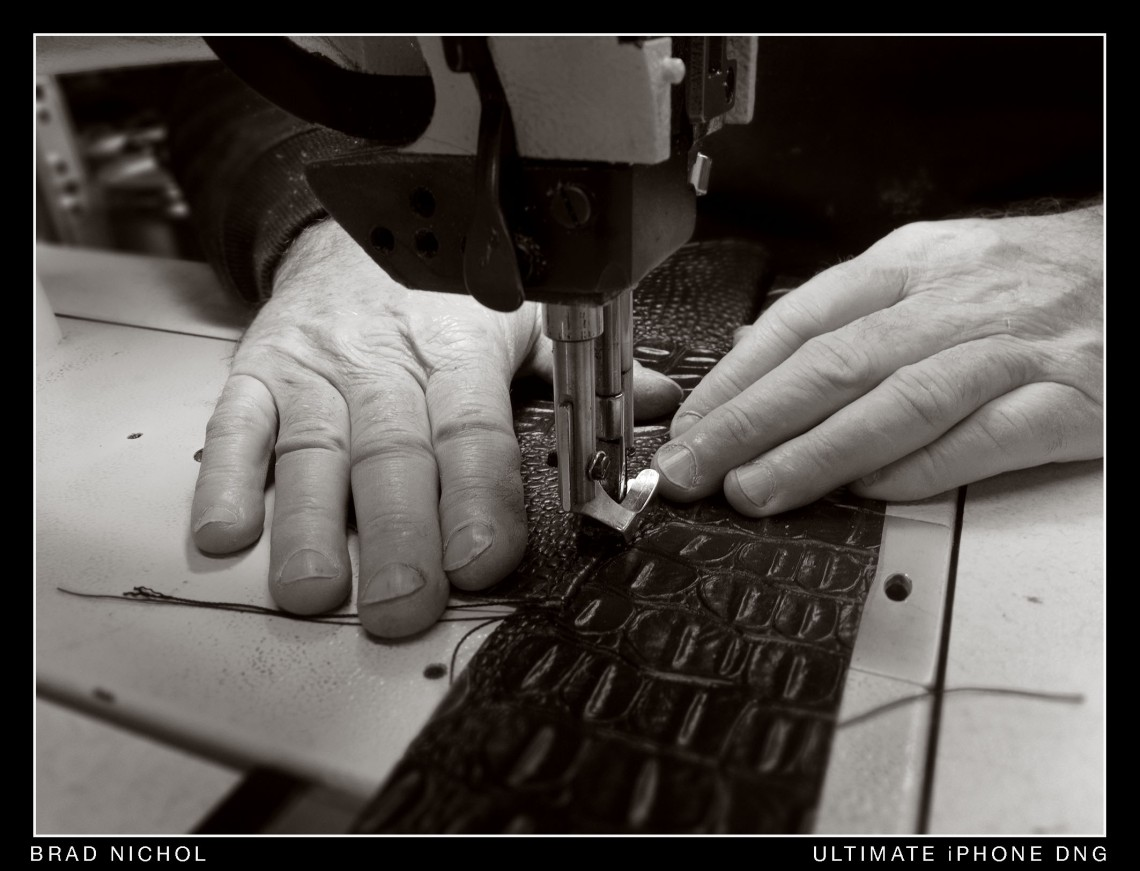 Industrial sewing machine sewing embossed leather.
