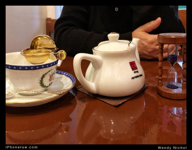 Tea on table in high end tea cafe, Ginza, includes timer, cup, pot and gold strainer.