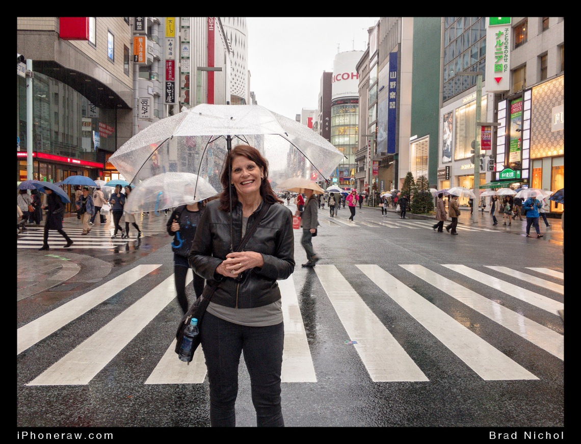 Lady standing in street under umbrella, Ginza, Japan, during Typhoon season, roads clear of cars.